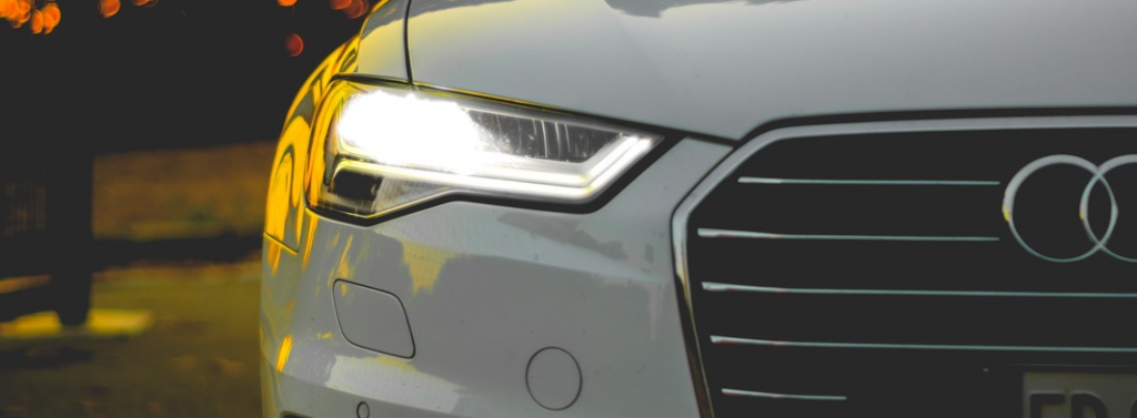 front of white Audi vehicle showing headlights and half of Audi badge