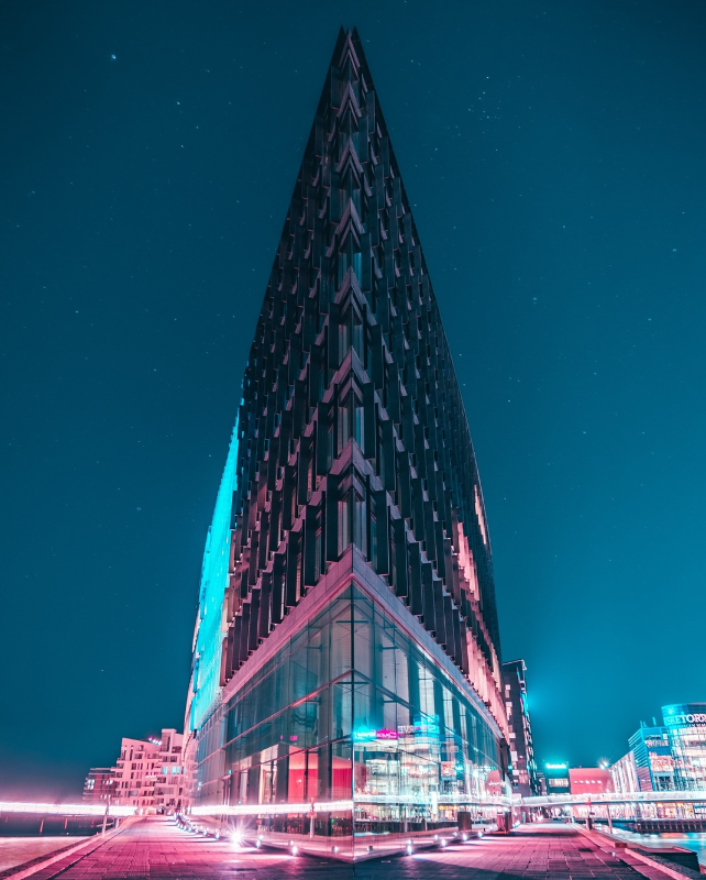 skyscraper building against night sky with neon pink lights