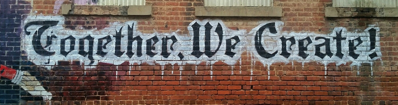 graffiti in gothic font reading 'together we create'