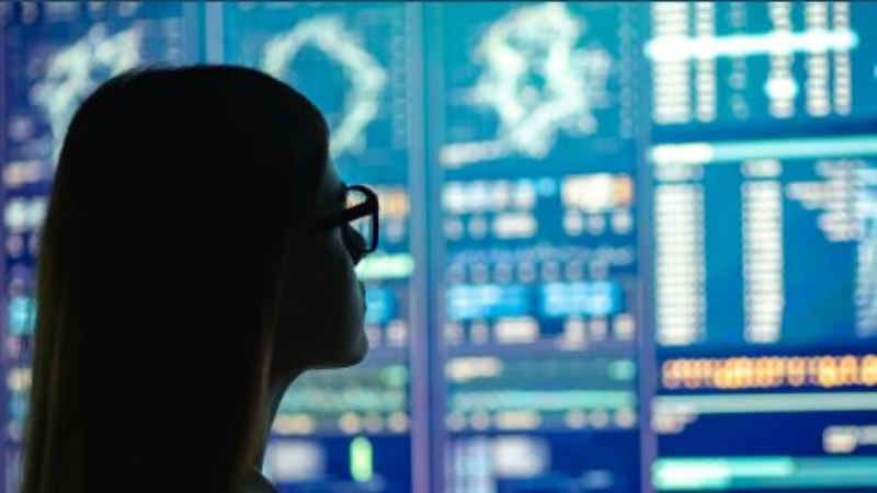 woman in silhouette in front of data display screens
