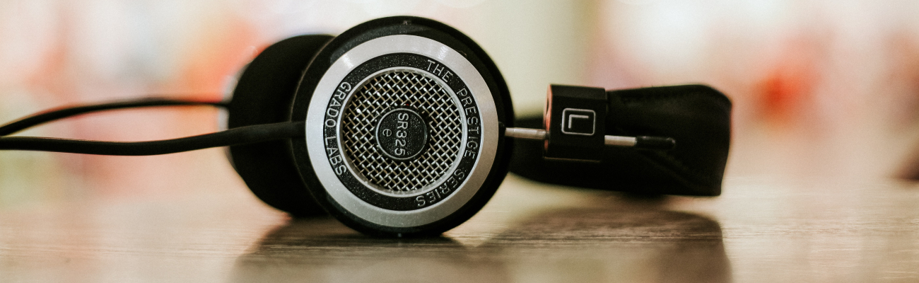 Close up of old style headphones lying on a wooden table
