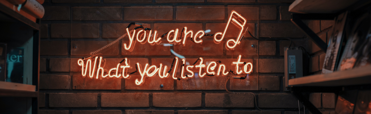 """Neon writing on a brick wall reads, """"you are what you listen to"""" with records on shelves"""