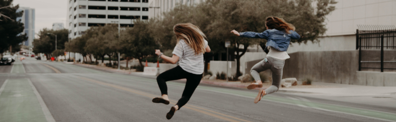 Empty city street scene with two men jumping for joy