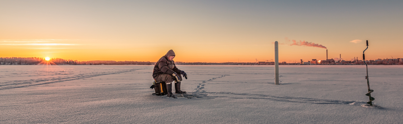 Man in isolation in a snow field at sunset with a factory in the distance